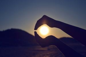 hands encircling sun
